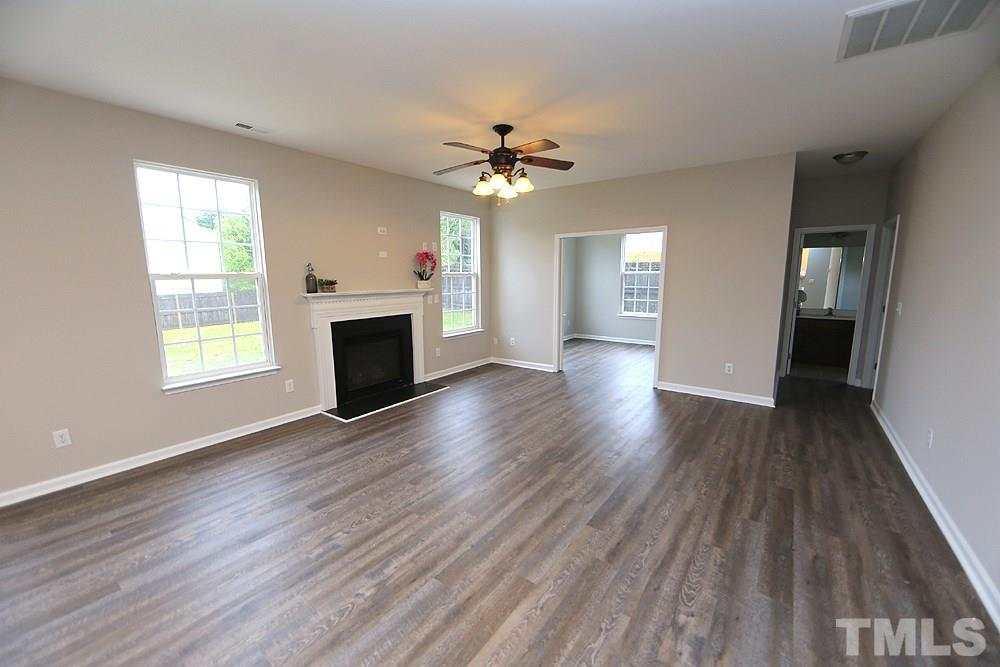 A view of the family room through to the adjacent office with windows on side and back.