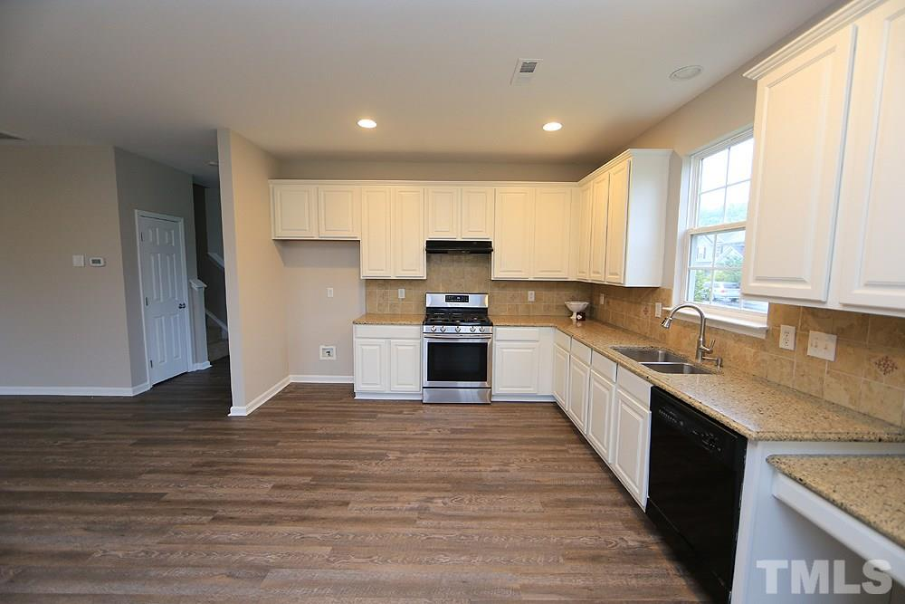 Another view of the kitchen with a gas range, tile backsplash and I think quartz counters