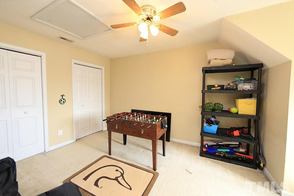 Laundry room is located between the garage and kitchen and offers shelving for additional storage.