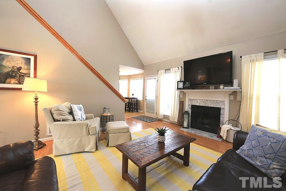 Spacious living room with cathedral ceiling, fireplace, and access to back deck.