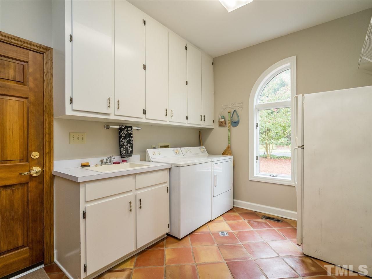 The laundry room is quite impressive and has a sink, built-in cabinetry and lots of storage options.