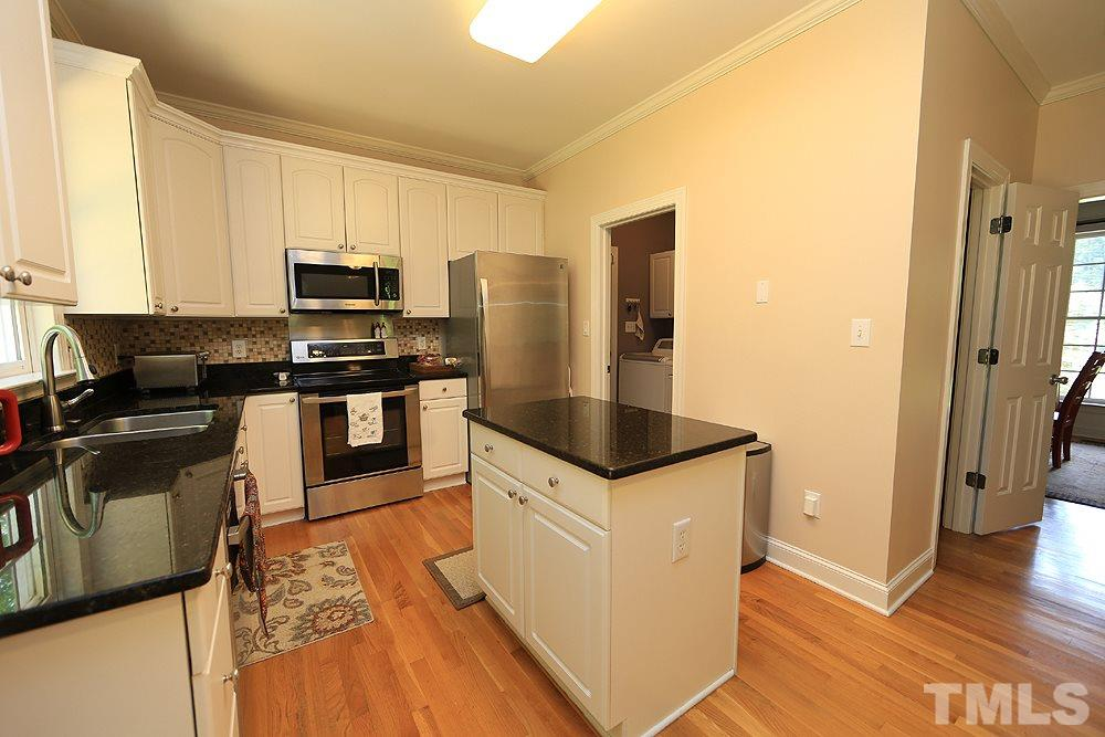 The kitchen also features an island and gleaming white cabinetry.