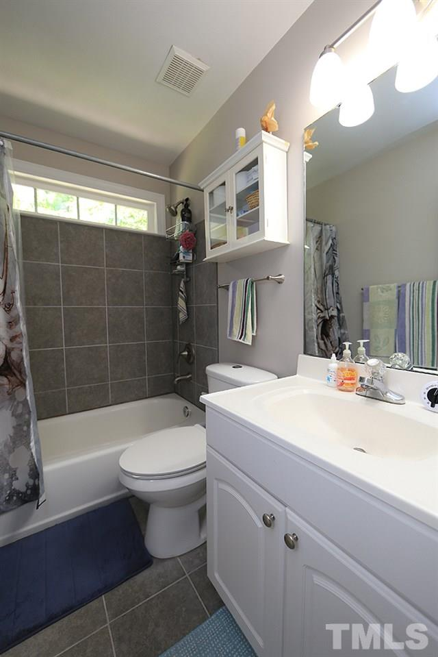 Recently renovated guest bathroom features tiled shower wall and floor and efficient dual flush toilet.