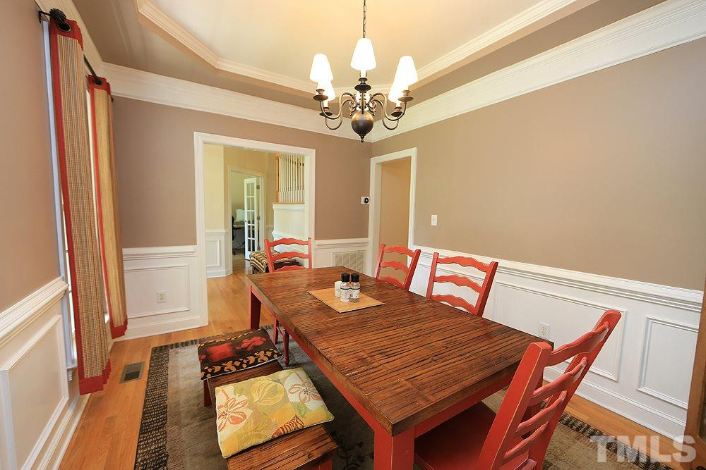 Elegant formal dining room with wainscoting and trey ceiling.
