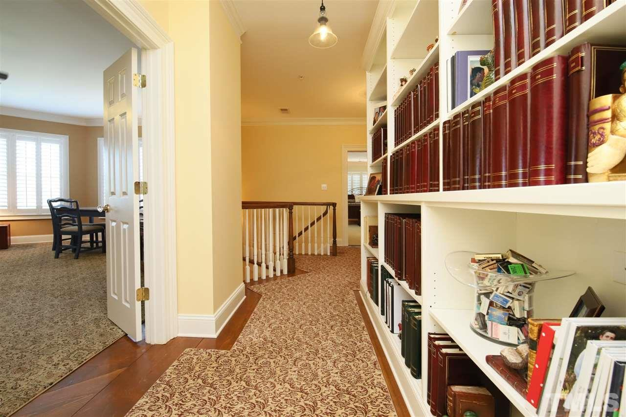 The hallway on the second floor features custom bookshelves just outside of the media room.