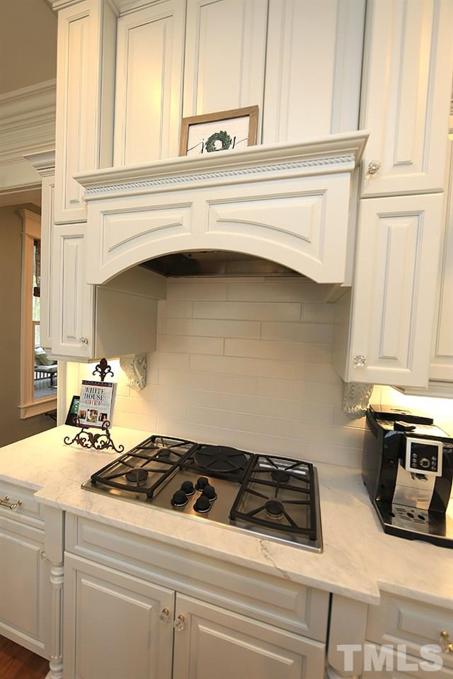 An up close view of the cooktop, cabinet detail & backsplash...the cabinets on both sides pull out for storage.  Notice elegant crystal style knobs on the cabinets & drawers. There are speakers in kitchen, scrn porch, master bath, office, fam rm & dining.