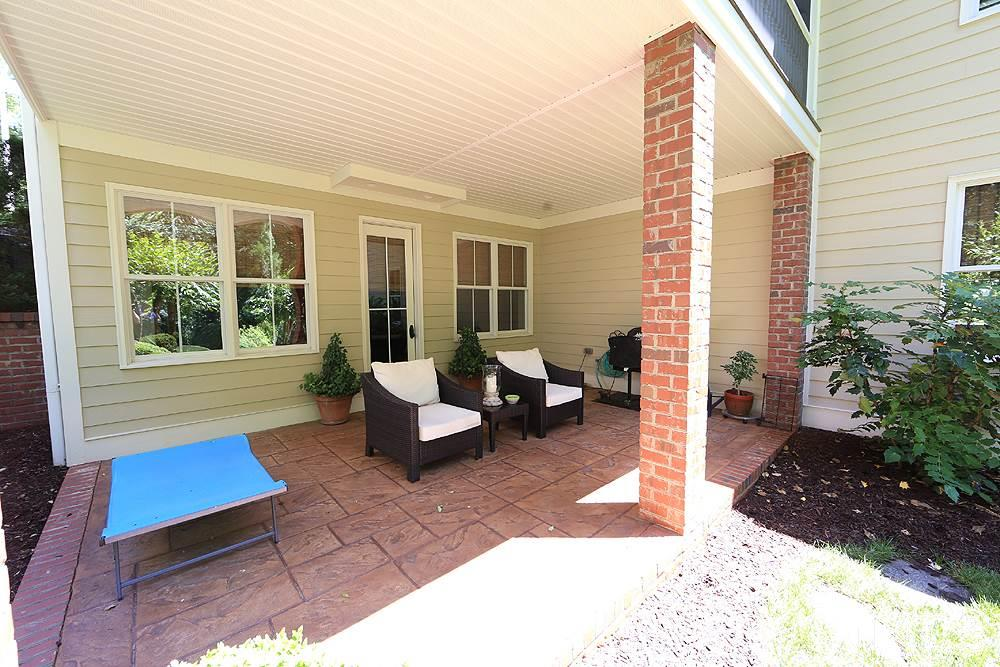 The covered patio beneath the screened porch has a stamped concrete floor and opens to the beautiful backyard.