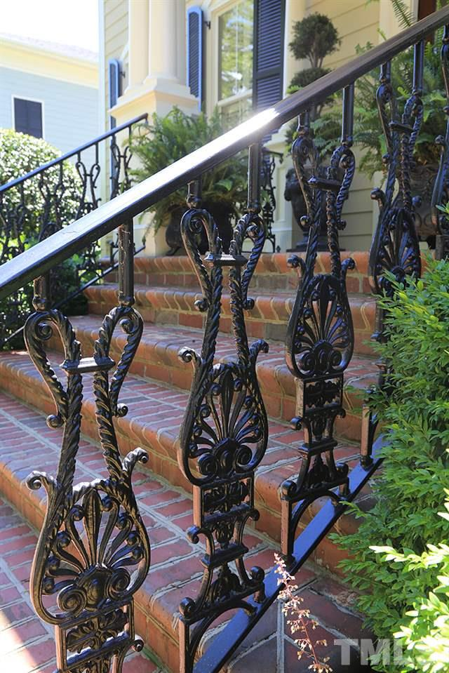The intricate and substantial, custom iron railings lead to the front porch and enclose the grilling deck.