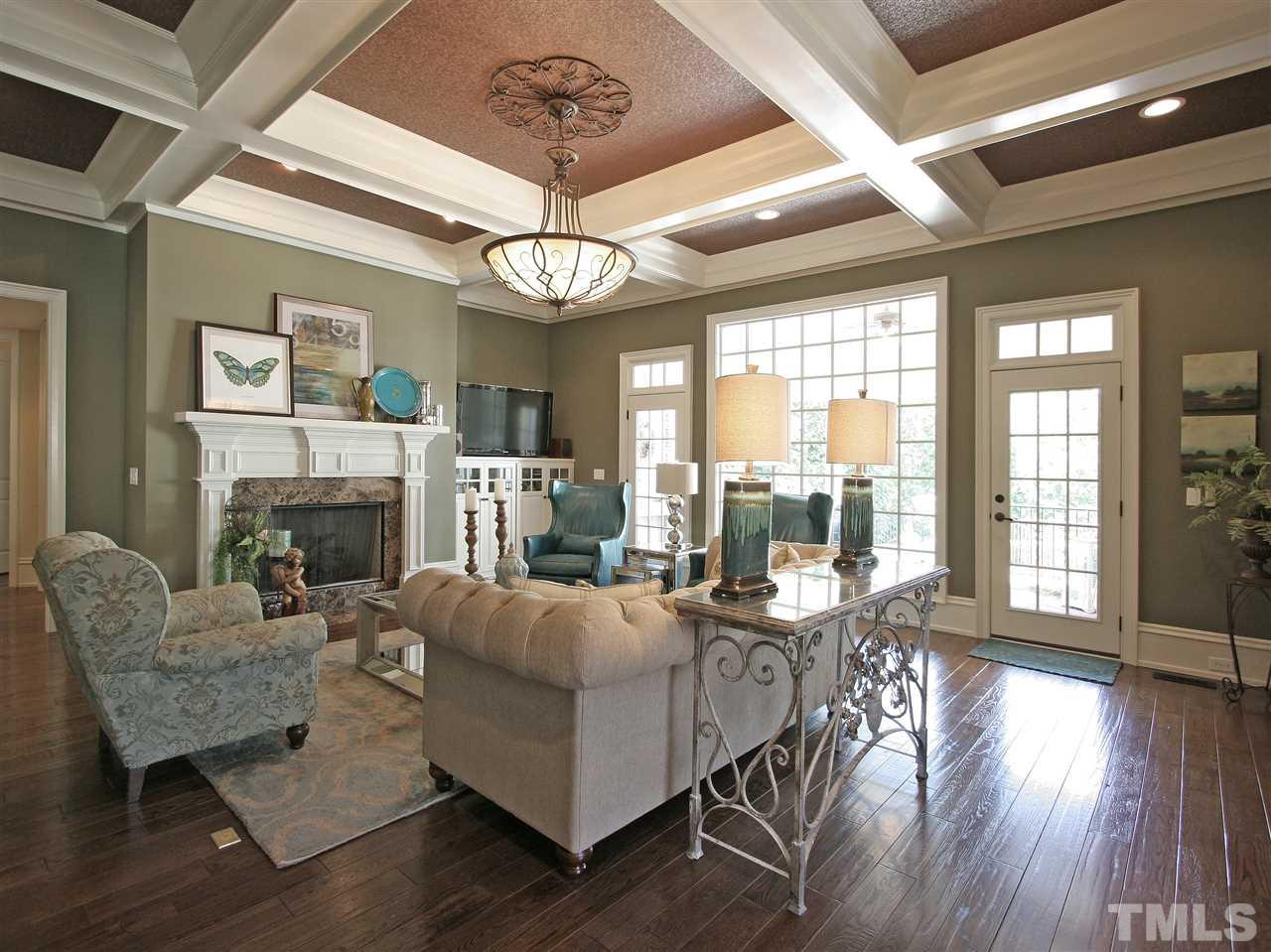 "The family room features an elegant coffered ceiling, cozy gas log fireplace with marble surround and hearth, and custom built-in cabinets. A large ""picture window"" and two 15-panel glass doors with transoms overlook a covered porch and patio area."
