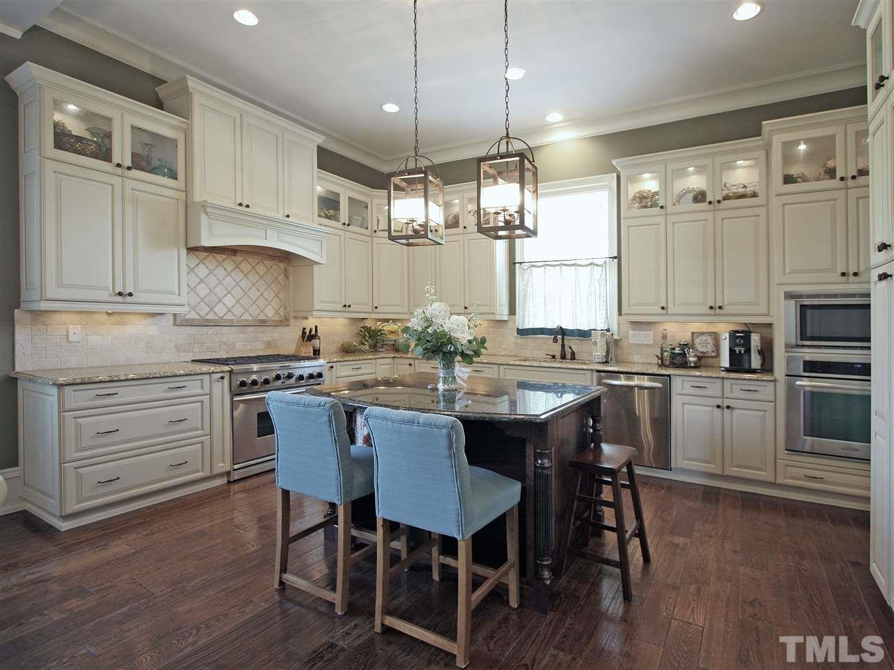 The kitchen has a great flow for cooking and for entertaining. Glass-front cabinets show off your glassware and decorative items. The central island provides seating, plus extra work space and storage. Pendant, under-cabinet, and recessed lighting.