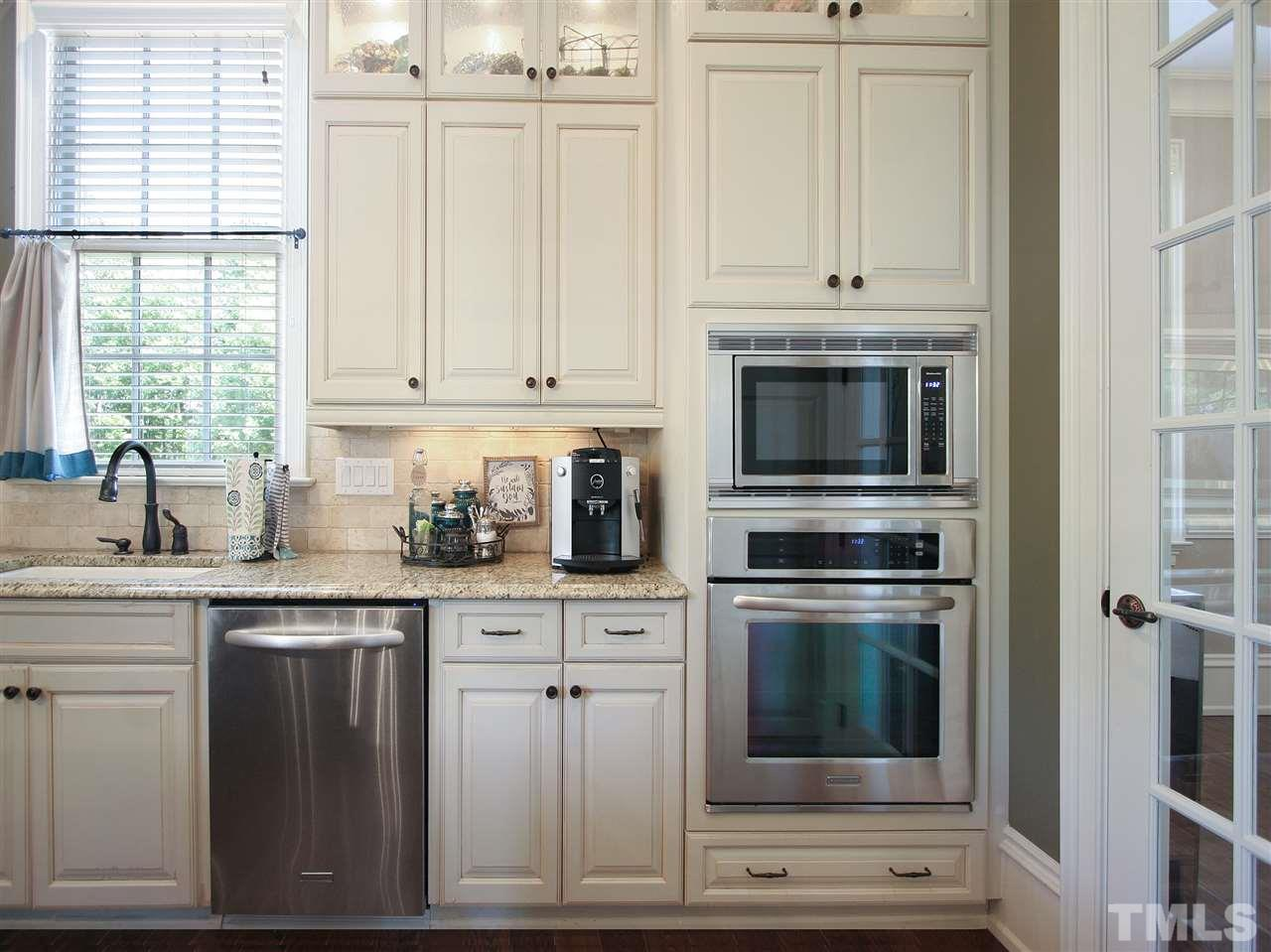 In addition to the range, the kitchen has stainless-steel built-in double wall ovens. Window over the sink overlooks the front lawn. The verdant tree-lined 14th tee and fairway are across the street.
