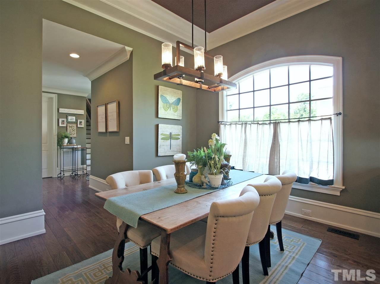 Linger over that second cup of coffee or tea in the delightful breakfast room. Note the arched window. Hallway to the left contains a built-in planning desk and accesses the side door, door to garage and laundry/mud room, and the home's second staircase.