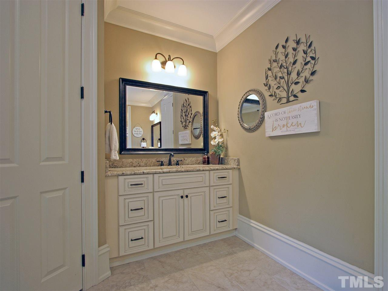 This view of the master bathroom showcases one of the two vanities. Note the beautiful cabinetry, granite countertops, oil-rubbed bronze plumbing and lighting fixtures, and the framed mirrors. Master bath has separate toilet enclosure as well.