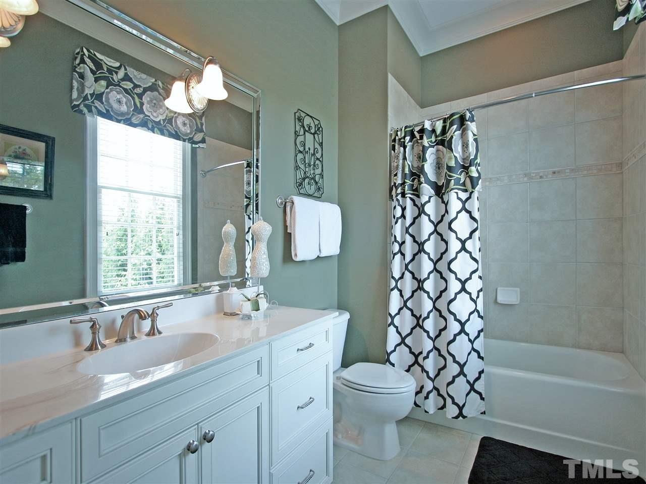The home has four full baths plus two half baths. This en suite full bath makes it's adjoining bedroom perfect for guests. Note the custom tile and framed mirror.