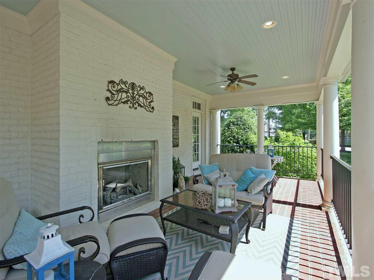 This south-facing covered porch has a cozy gas-log fireplace for the cooler months and ceiling fans for the warmer seasons. Enjoy it year 'round. Stately columns, wrought iron railings, and historically accurate paint choices carry the Charleston theme.