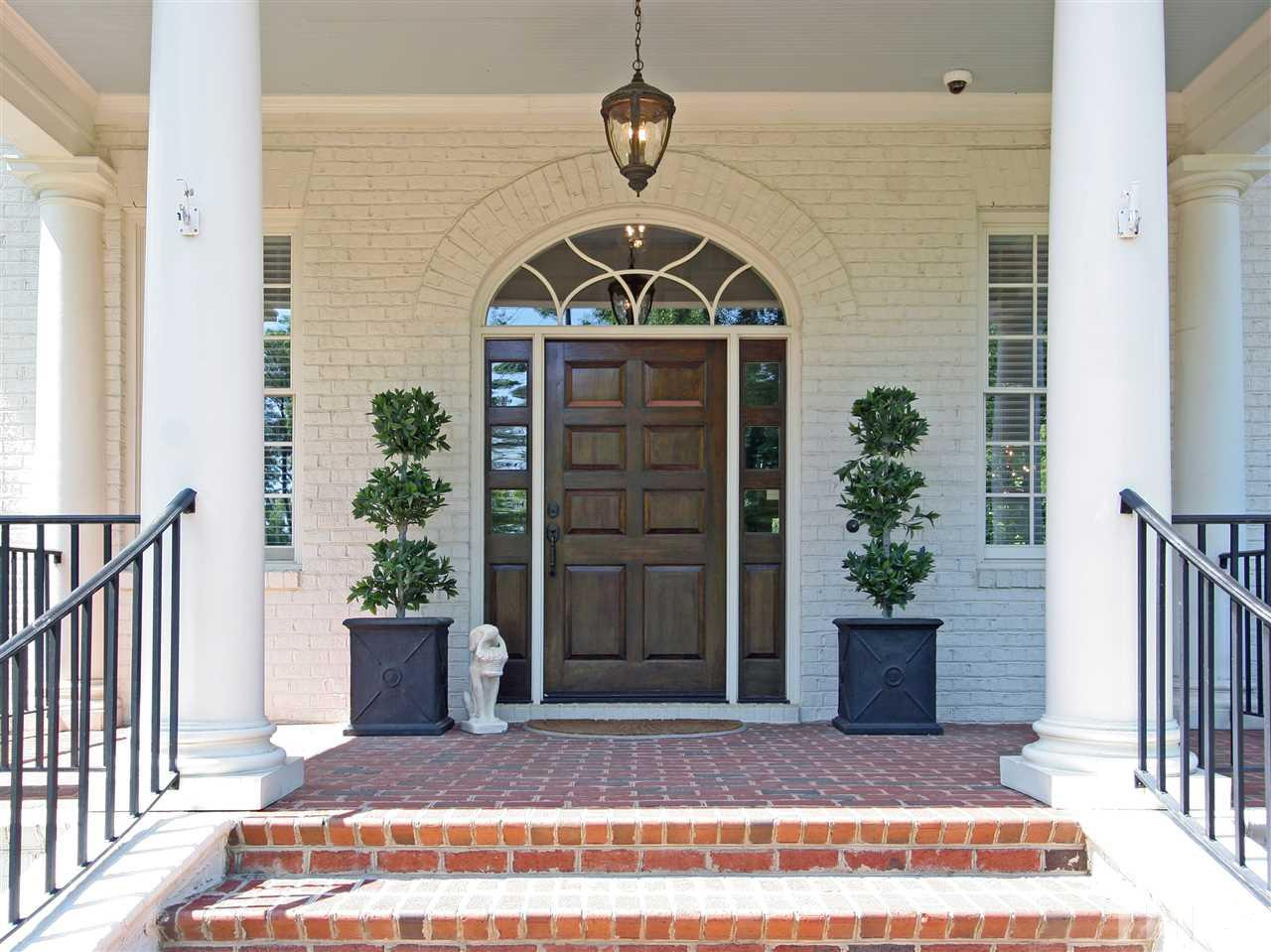 A beautiful solid-wood front door greets you and your guests. This delightful rocking-chair-style front porch is one of five covered porches that grace the home. 12 Oaks is a friendly, walkable neighborhood with sidewalks adorning tree-lined streets.
