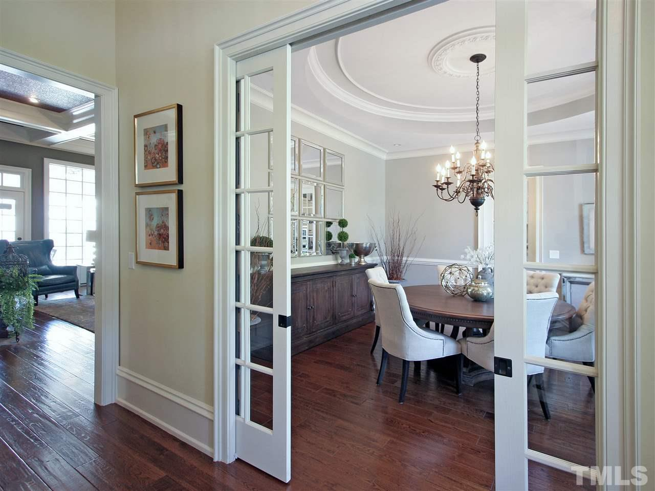 To your right as you enter the foyer is this delightful formal dining room. Note the pocket French doors, another nod to historic Charleston styling. Also note the circular trey ceiling with central medallion and the hardwood flooring.