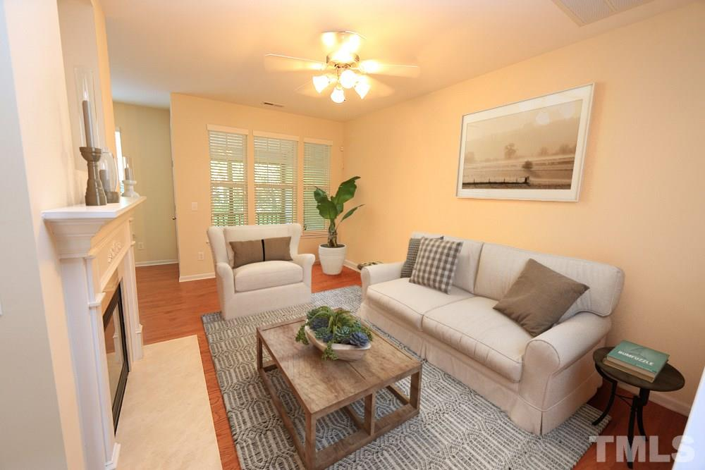 Virtually staged to help buyers imagine the space. Beautiful NEW hardwood floors, gas logs -- the perfect gathering spot.