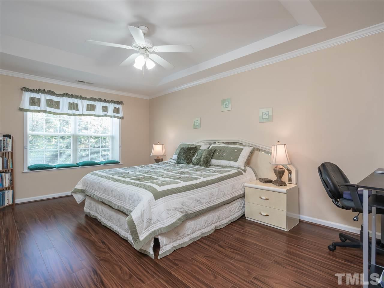 Now this is what I call a Master bedroom! Wood look flooring, fan, window seat, tray ceiling and moldings added for that custom touch!