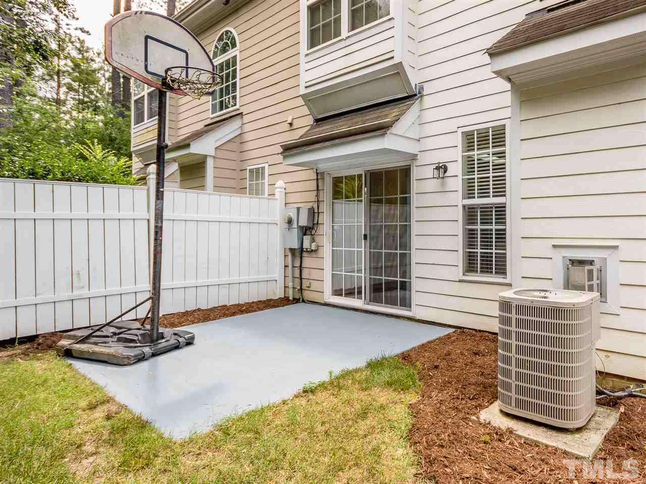 Patio area! Basketball hoop can convey! White fences on either side and greens in the rear! Your own private oasis!