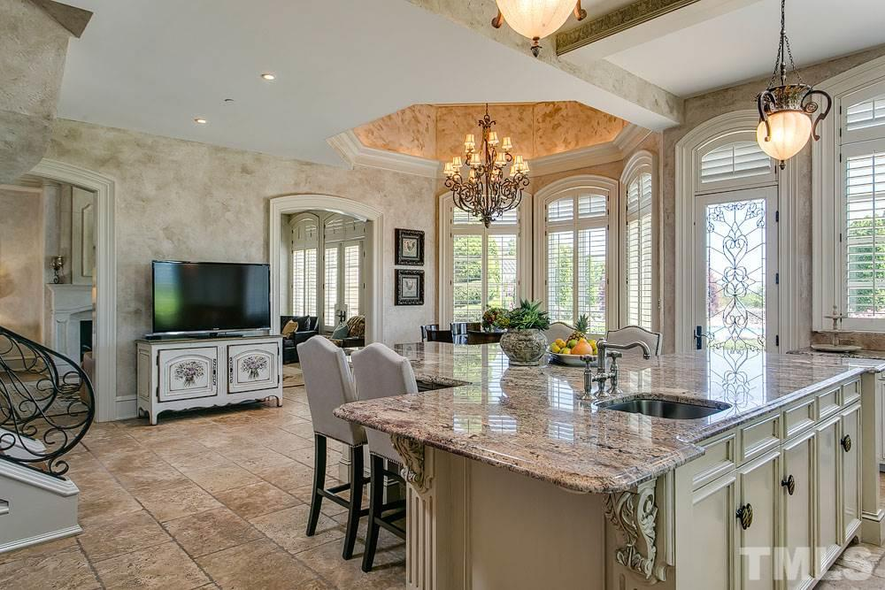 The stunning kitchen features a large breakfast room, enormous island, scullery pantry, top appliances, kitchen office and butler pantry.