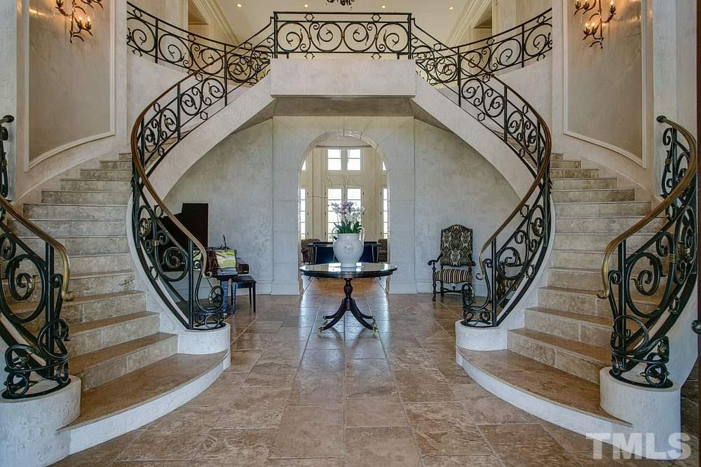 Exceptional custom work with double stone stairways, wrought iron railings, sconces and chandelier were forged by local artisan.