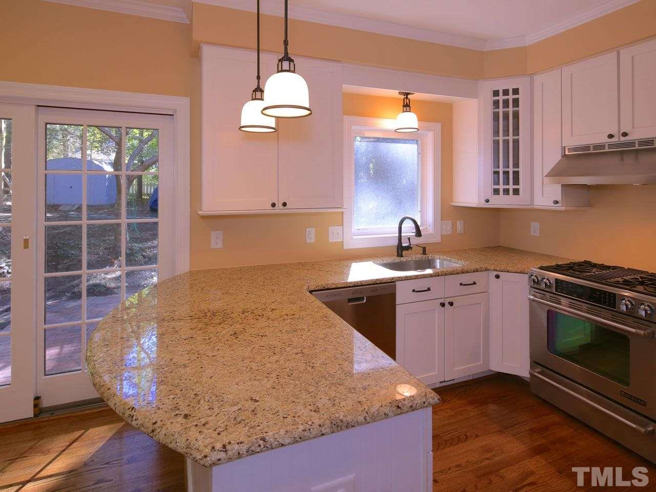 The large, curved granite counter makes this the perfect eat-in kitchen. (The bar stools do not convey).