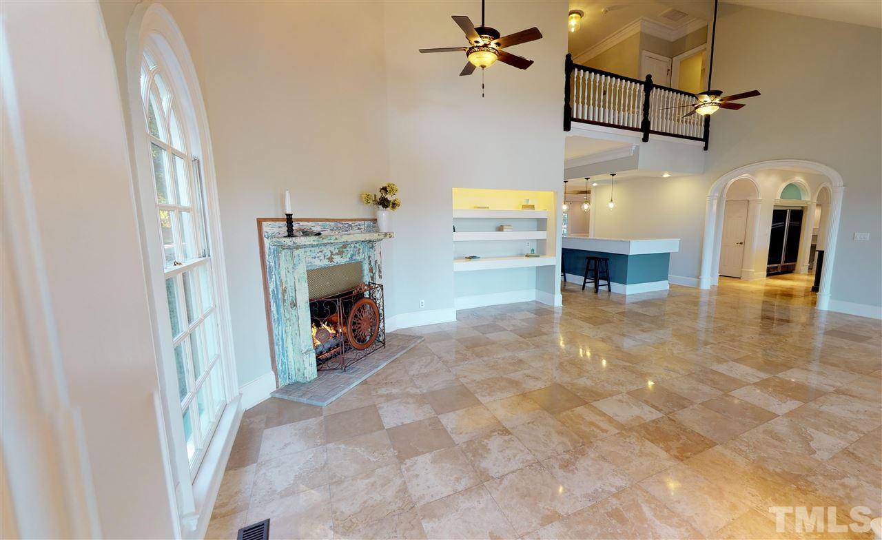 Fireplace with brick hearth and custom built shelves, sunlight filled room for cheerful days