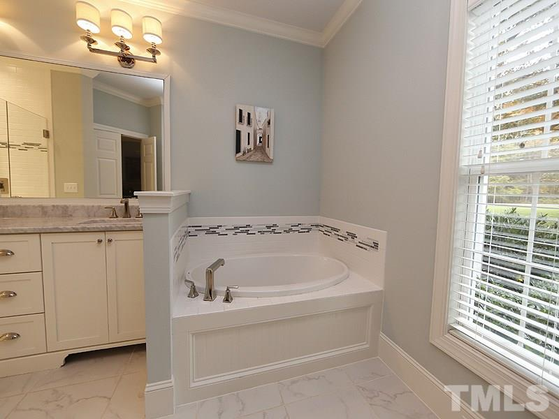 This Master Bath features Dual Sinks, Granite Countertops, Tub, and large tiled Shower w/ a frameless Glass Enclosure.