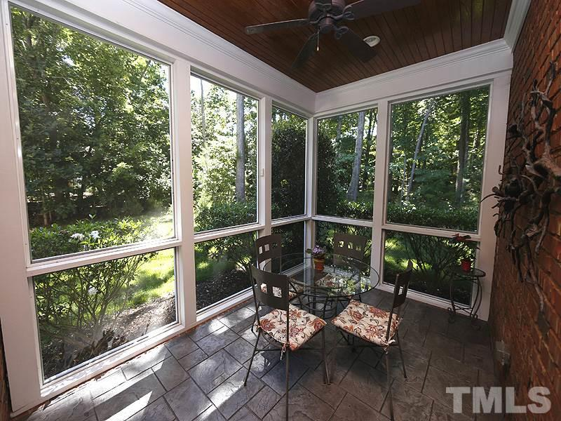 The owners love having their breakfast in this sweet space overlooking aromatic gardenia bushes. Ceiling fan, stained bead board ceiling and stamped concrete floor.