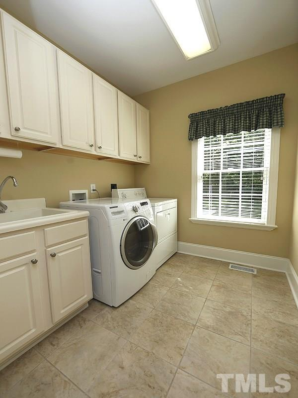 Between the kitchen and garage is the well designed laundry room...lots of cabinets, window, laundry tub. Tiled flooring here and in all the full bathrooms.