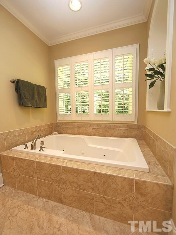 Large jetted tub with tile surround has decorative niche on one wall, plantation shutters on the windows.