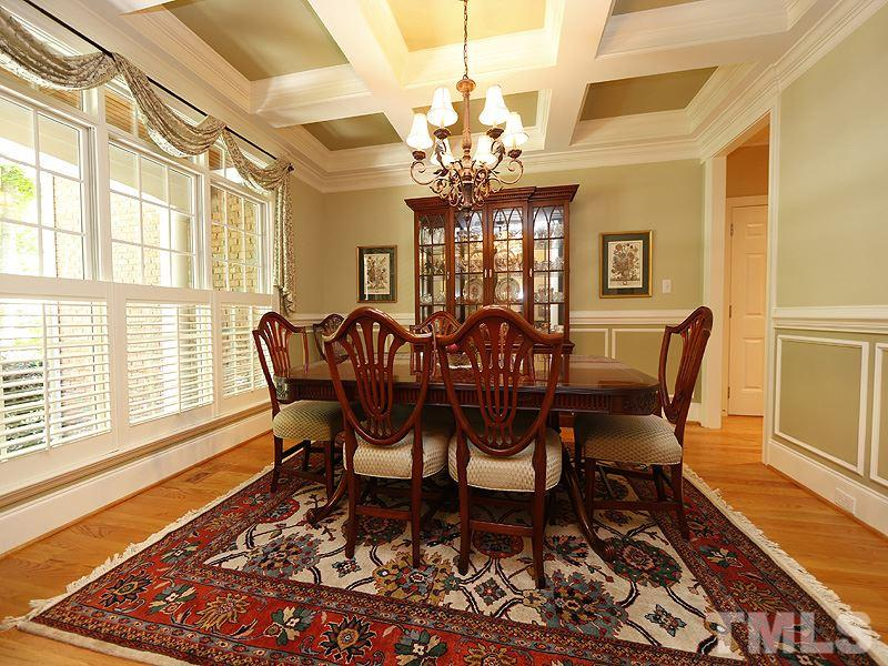 To the left of the foyer, flanked by twin columns,  you'll find the gracious dining room, with coffered ceiling, chair rail molding and wainscoting. plantation shutters.