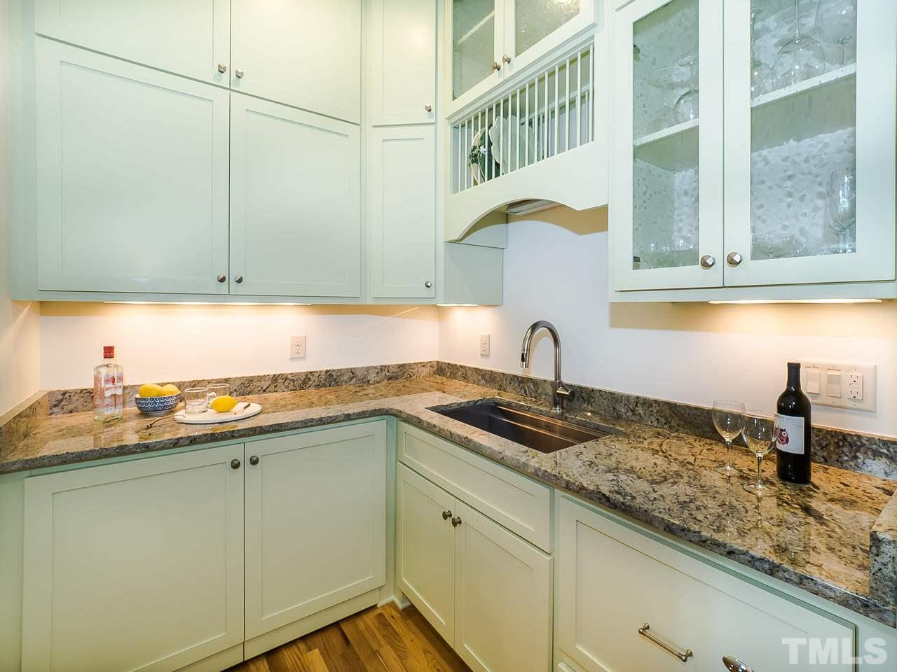 Gorgeous painted cabinetry with abundant storage, second dishwasher, hidden storage, granite counters & custom sink.