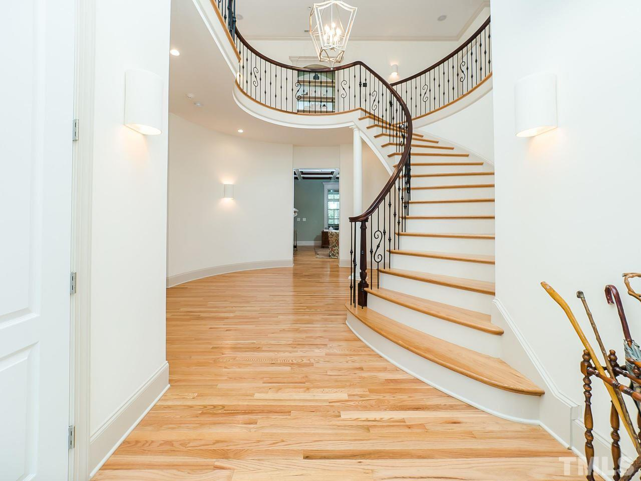Grand Foyer with dramatic sweeping staircase.  Features wrought iron railing. Gorgeous hardwoods throughout the main areas.