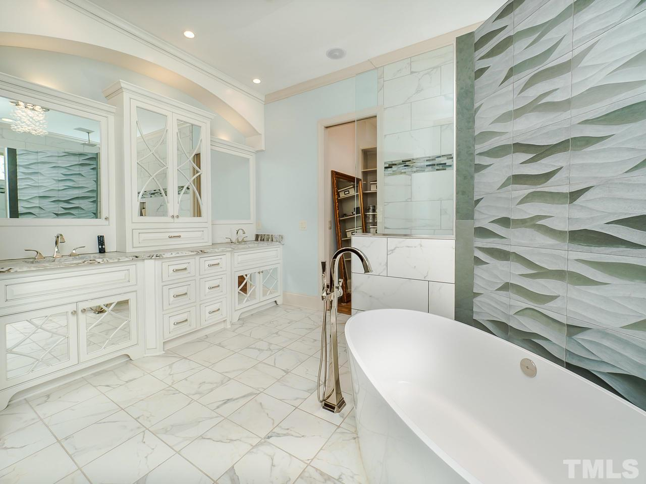 Gorgeous! Stunning custom cabinetry, custom tile feature wall, double walk-through shower and free-standing volcanic, Victoria+Albert tub. TV hidden behind mirror for viewing while getting ready or relaxing in your tub.