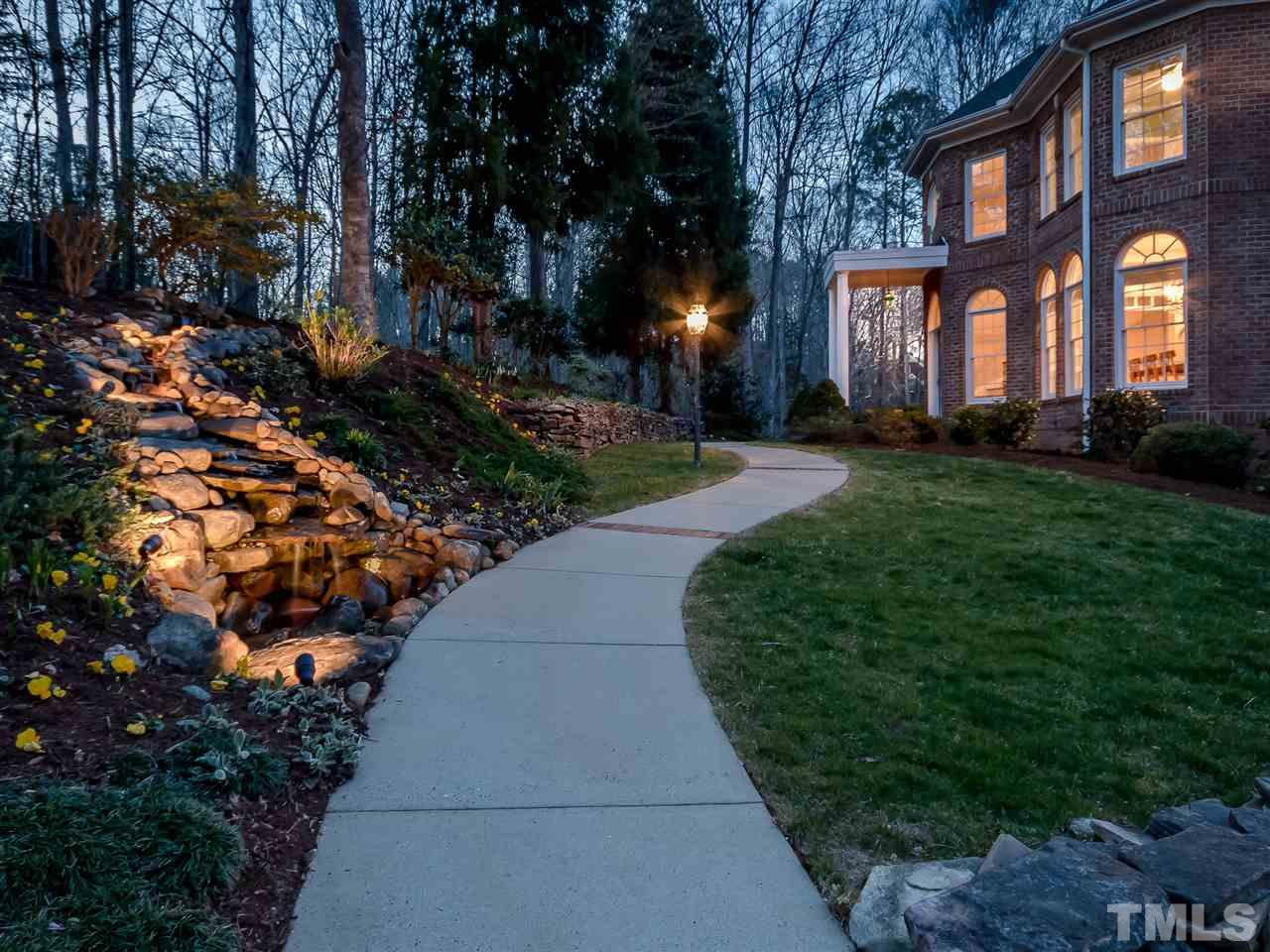 Welcome home through your own enchanted forest with custom, stone waterfall and lightscaping.