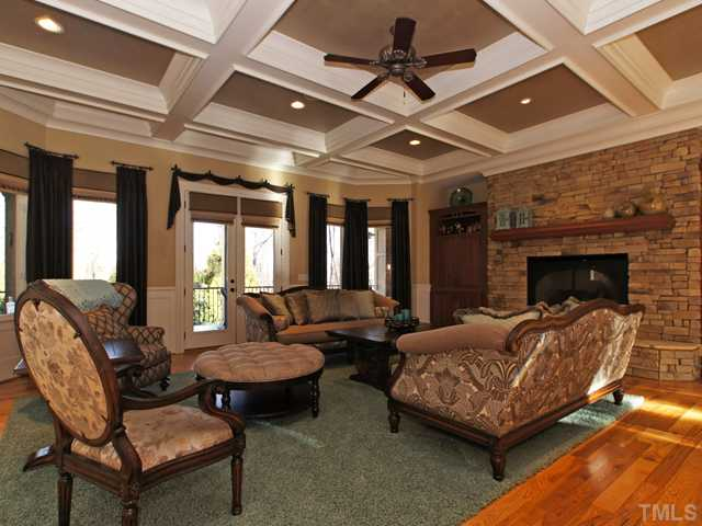 Great room with stone fireplace overlooks the pool and covered porch area!