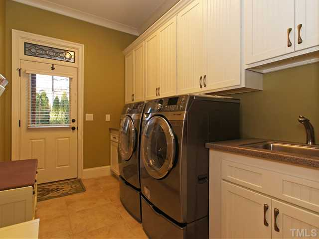 Laundry room w/side driveway entrance and plenty of cabinetry for storage.