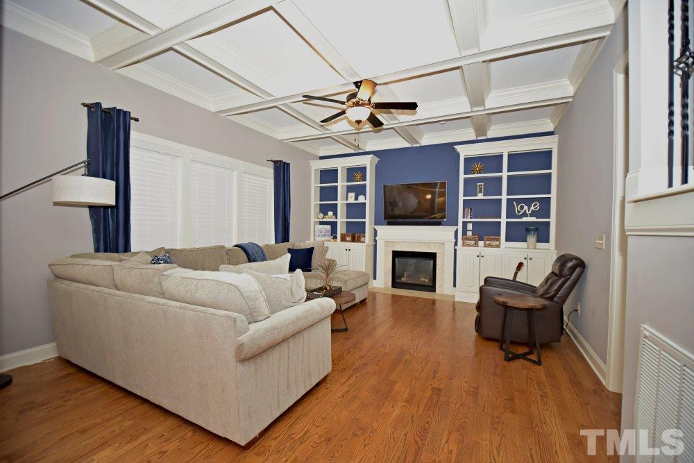 Award winning, heavily detailed coffered ceiling, custom built in cabinets add charm to this cozy family room.