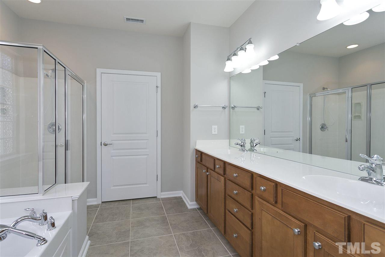 Master bath with beautiful cabinetry, double sinks and separate water closet area.