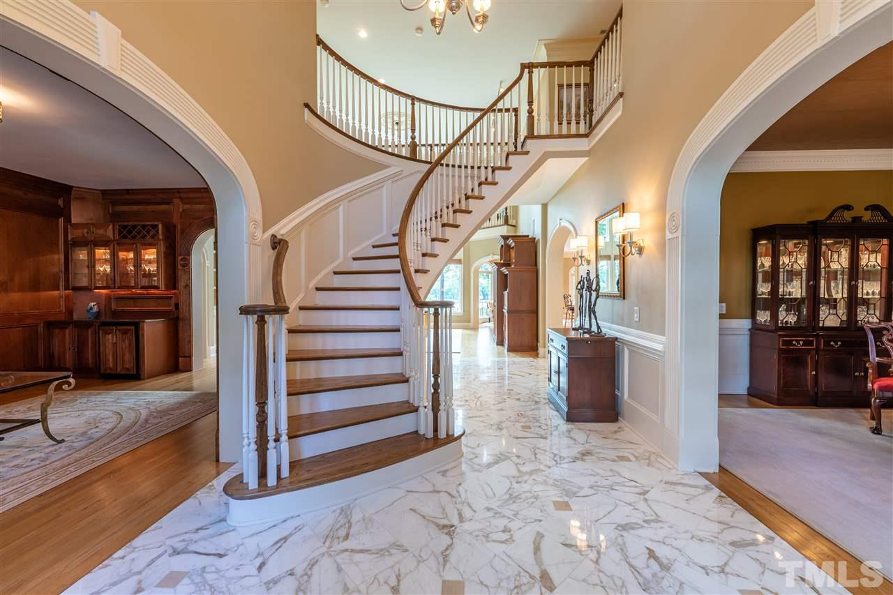 Grand Foyer features Sweeping Staircase & Marble Floor.
