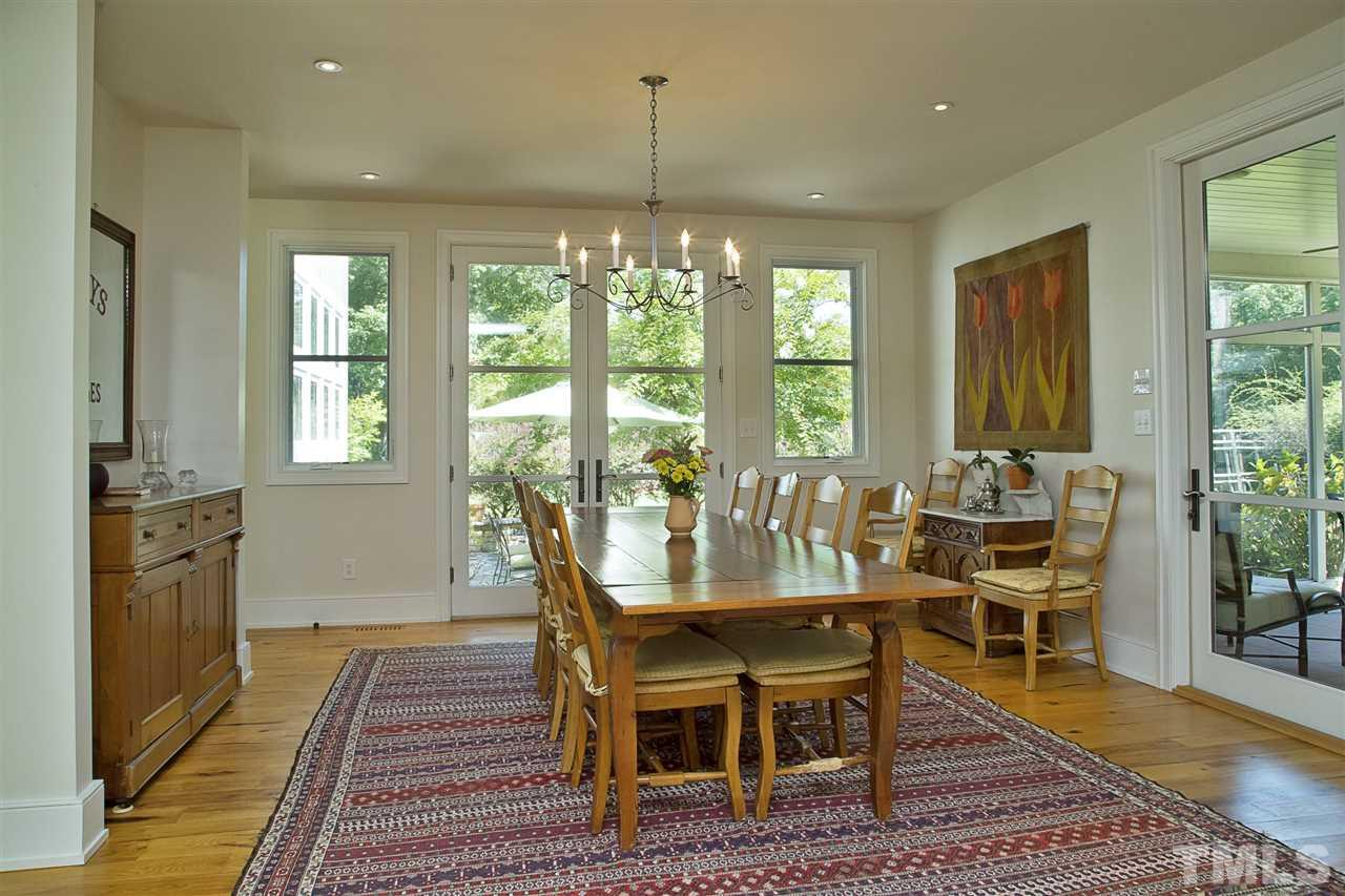 The large dining room is open to the kitchen. Glass doors open up to a wonderful screened porch on one side of the room and to a patio on another side. Cased openings lead to the living room and the foyer.