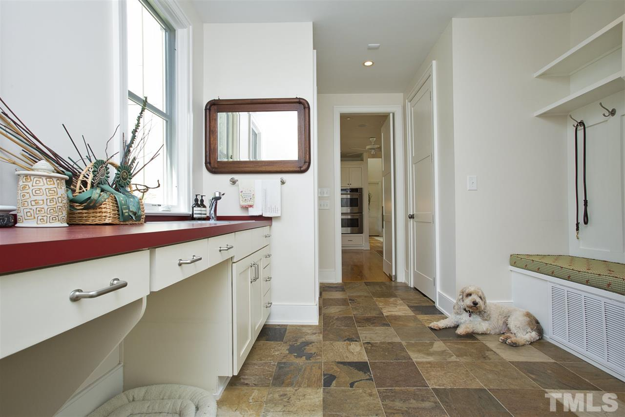 Upon entering the home from the side entry, you encounter a fabulous slate floored mudroom, complete with lots of counter space, a sink, half bath, pantry, broom closet and cubbies! No, the dog is not included.
