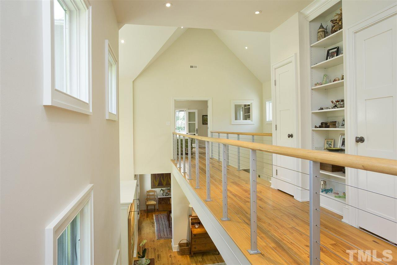 Take the custom stair treatment of glass and metal with hickory bannisters to the second floor. Immediately you will find two bedrooms, a full bath and a laundry room. Take the bridge across the middle of the home to enjoy views below.