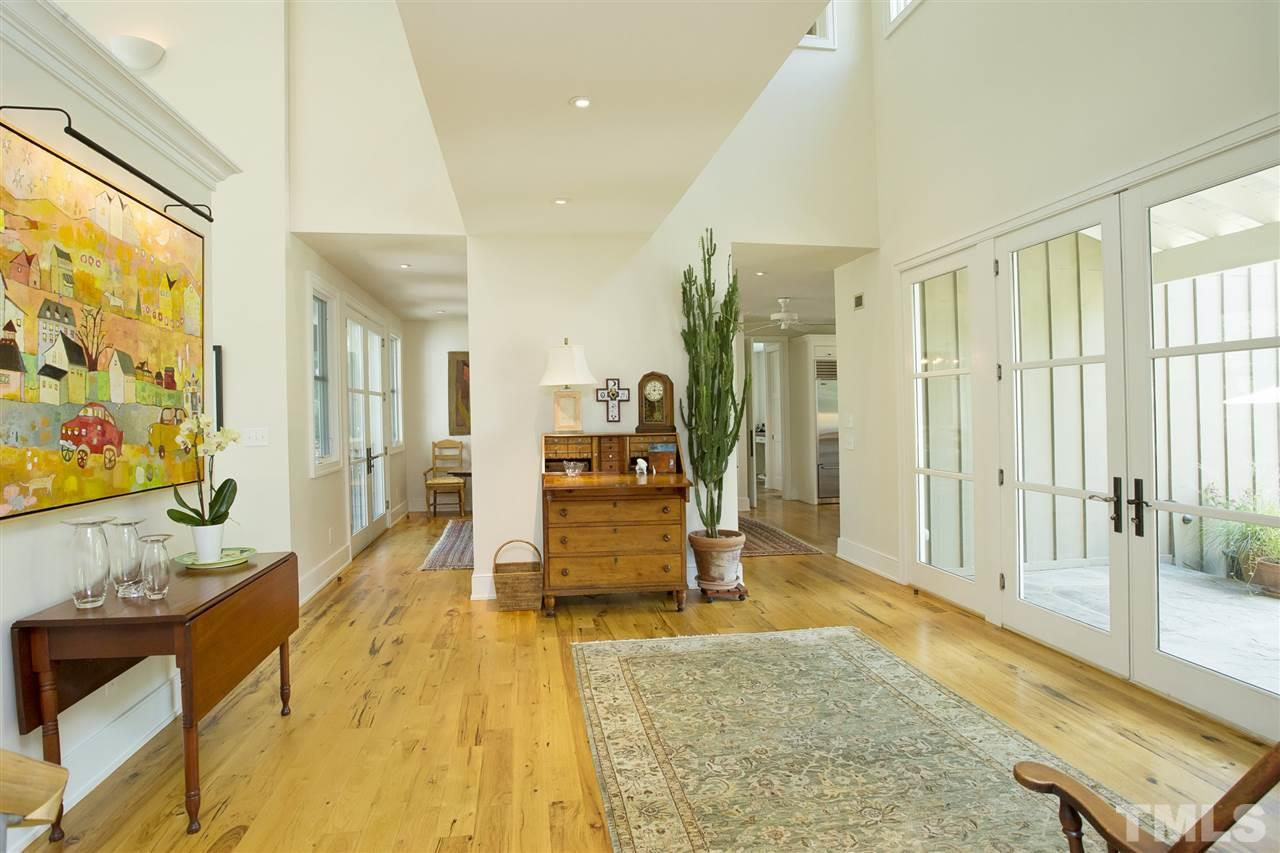 As you walk into the foyer from the outside, just to the right are cased openings leading to the kitchen and dining room. Nine ft or two story ceilings along with eight ft sold wood or glass paned doors.