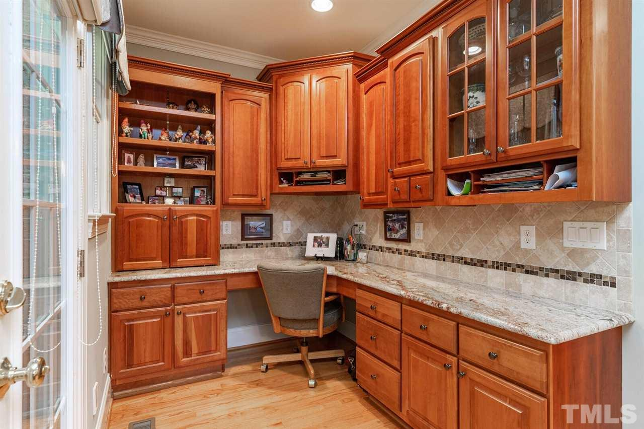This office is off the kitchen in the back of the house. beautiful cabinets and granite. Hidden away but yet open. Door goes to the Four season room off the back of the house and the deck.