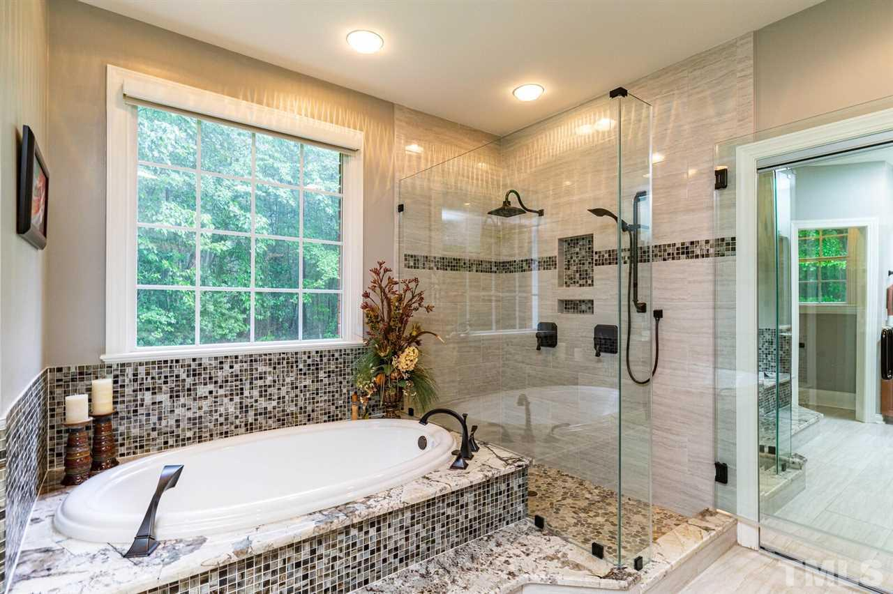 Owner Bathroom facing the backyard. Beautiful tile and stone glass shower. Soaking tub.