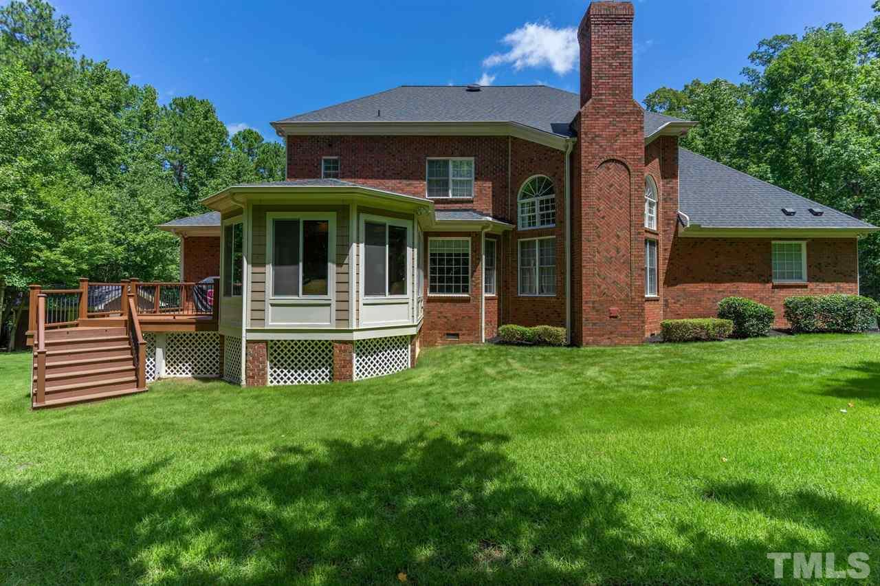 Back of the all brick home. Beautiful grass, Sunroom and Deck. Deck has Trek Deck.