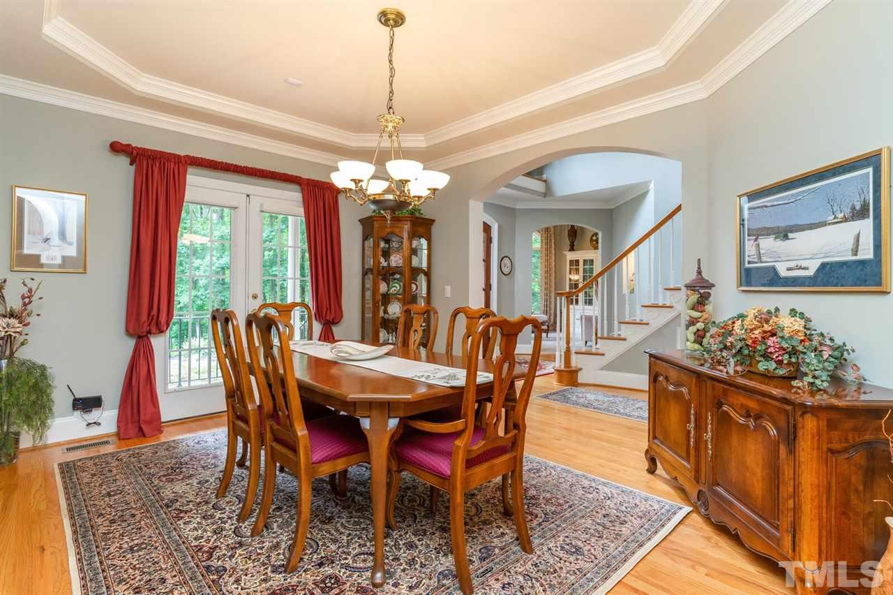 Dining room at front of house with a door to the front porch. Tray ceiling and hardwood floors.